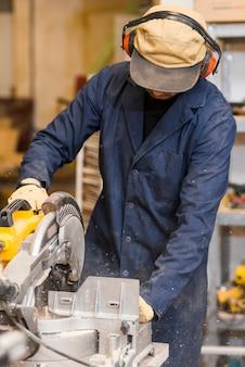 Männlicher tischler, der einige elektrowerkzeuge für seine arbeit in einem woodshop verwendet