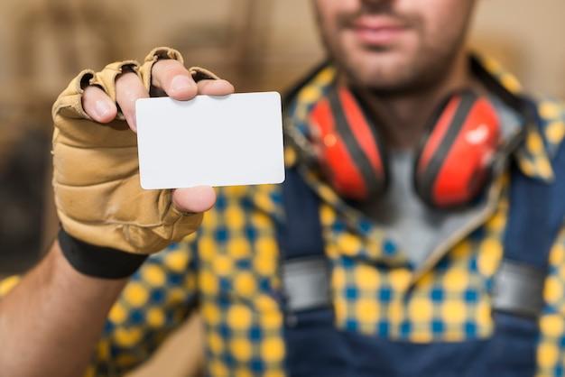 Männlicher tischler, der leere weiße visitenkarte zeigt