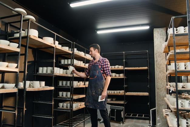 Männlicher töpfer mittleren alters in hemd und schürze zählt die keramik in den regalen und notiert ihre nummer in seinem notizbuch. grafik und kreatives konzept.