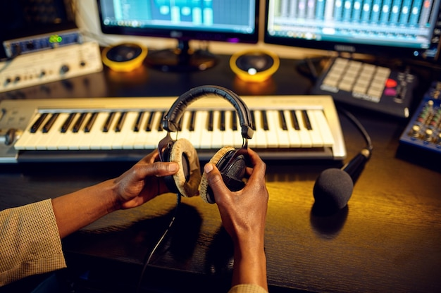 Männlicher toningenieur hält kopfhörer am mischpult, aufnahmestudioinnenraum im hintergrund. synthesizer und audiomixer, musikerarbeitsplatz, kreativer prozess