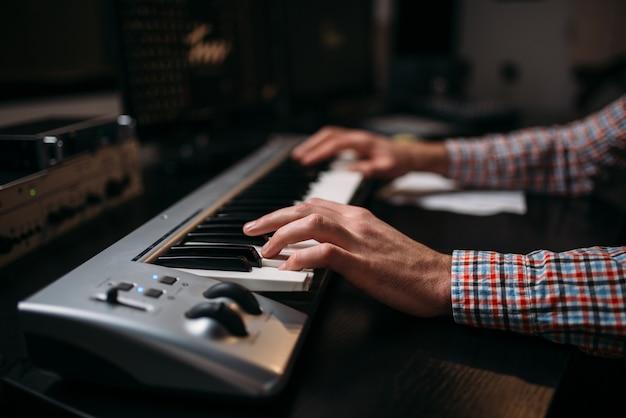 Männlicher tonproduzent hände auf musikalischer tastatur, nahaufnahme. digitale audioaufzeichnungstechnologie.