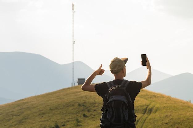 Männlicher tourist auf wanderreise freut sich über mobilfunkverbindung