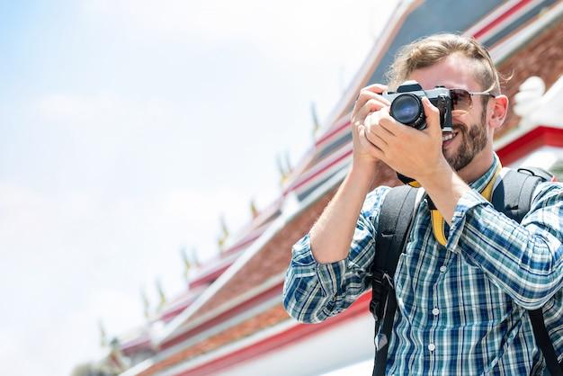 Männlicher tourist, der foto beim reisen auf ferien in bangkok thailand macht