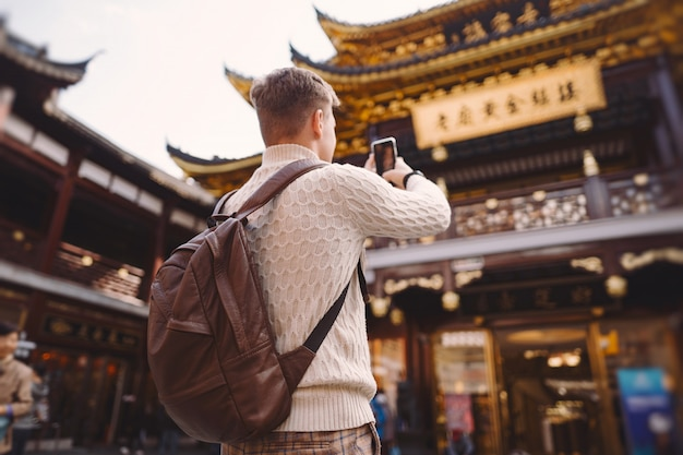 Männlicher tourist, der fotos einer pagode an yuyuan-markt in shanghai macht
