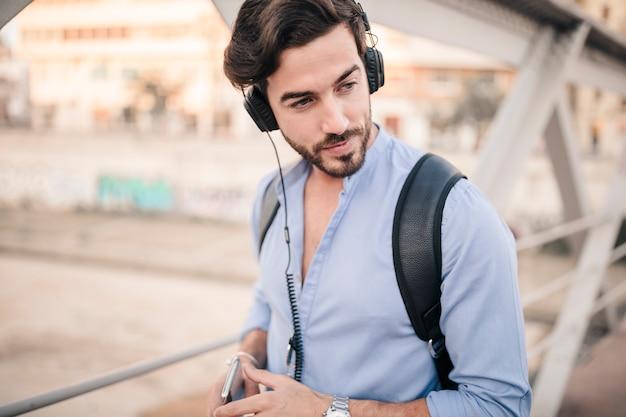 Männlicher tourist, der musik auf kopfhörer hört