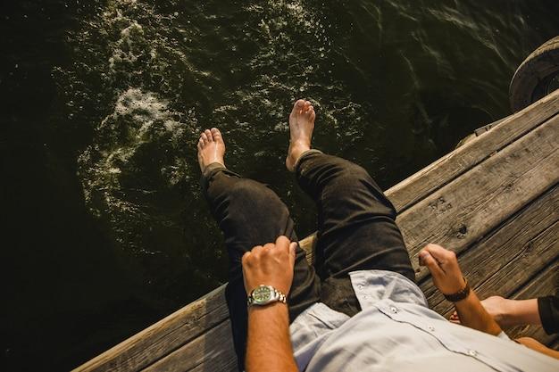Männlicher tourist, der seine füße im meerwasser, kornfilm hinzugefügt erneuert.
