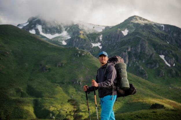 Männlicher tourist, der vor bergen steht