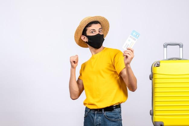 Männlicher tourist der vorderansicht im gelben t-shirt, das nahe gelbem koffer steht, der reiseticket hält