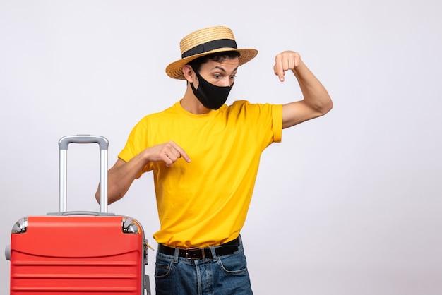 Männlicher tourist der vorderansicht mit gelbem t-shirt und rotem koffer
