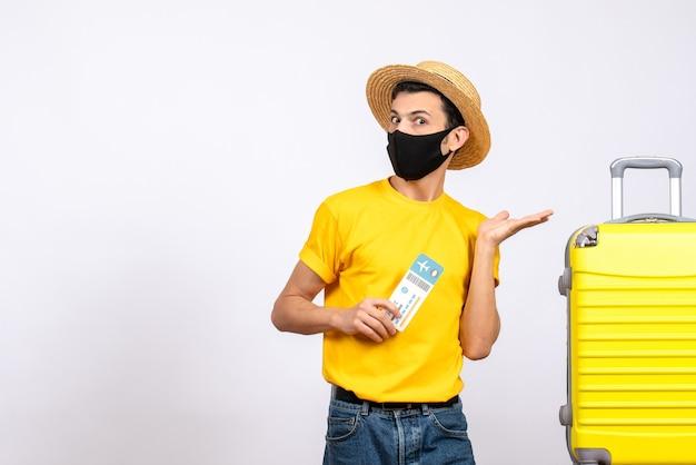 Männlicher tourist der vorderansicht mit strohhut, der nahe gelbem koffer steht, der reiseticket hält
