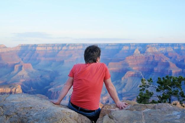 Männlicher tourist des mittelalters, der auf stein sitzt und vom grand canyon von mather point schaut