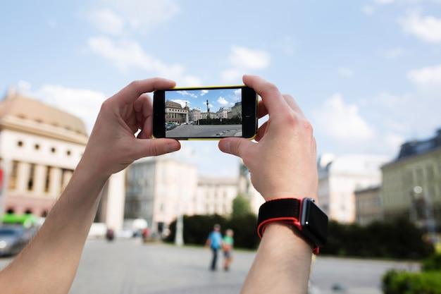 Männlicher tourist macht foto auf dem handy. nahaufnahme