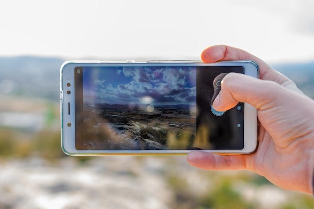 Männlicher tourist macht foto mit handykamera