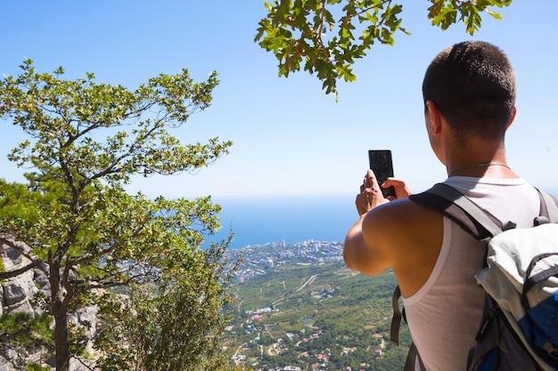 Männlicher tourist macht fotos auf einem smartphone mit schöner aussicht auf das meer in einer bergregion