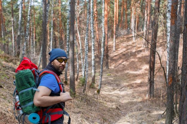 Männlicher tourist mit einem rucksack im wald. nahaufnahme portrarit.