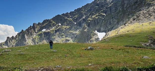 Männlicher tourist mit einem rucksack klettert auf die spitze des berges. altai