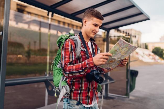Männlicher tourist mit rucksack an bushaltestelle