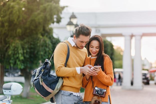Männlicher tourist mit rucksack, der telefonbildschirm mit ernstem gesichtsausdruck betrachtet