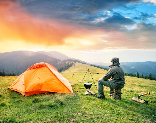 Männlicher tourist sitzt auf baumstamm nahe orange zelt in den bergen