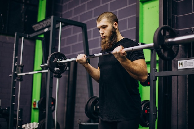 Männlicher trainer, der im fitnessstudio trainiert