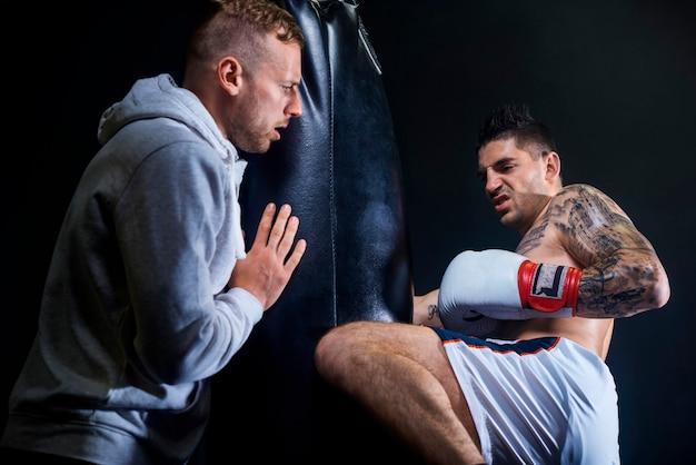 Männlicher trainer, der muskulösen boxer unterstützt