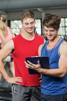 Männlicher trainer, der über leistung in der turnhalle sich bespricht