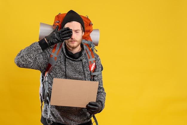 Männlicher tramper mit lederhandschuhen und rucksack, der eine leere pappe hält und die hand auf sein auge legt