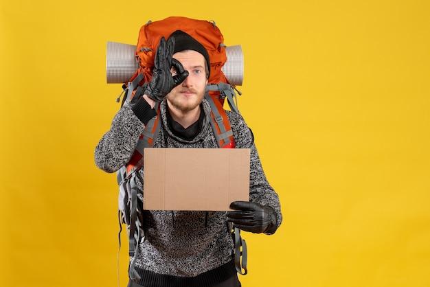 Männlicher tramper mit lederhandschuhen und rucksack, der eine leere pappe hält und vor seinem auge gestikuliert