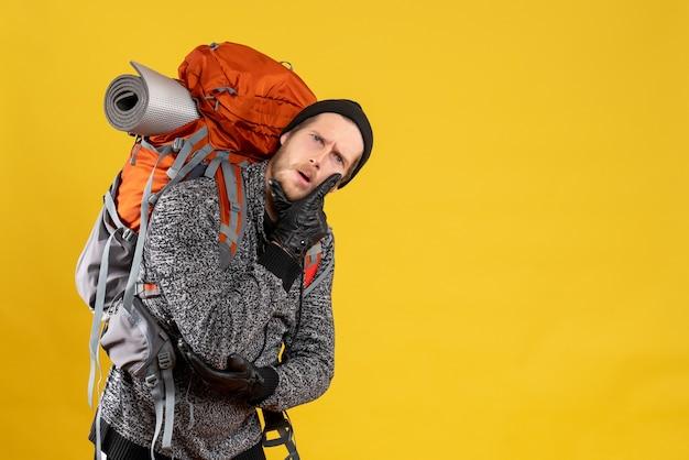 Männlicher tramper mit lederhandschuhen und rucksack, der hand auf sein kinn legt