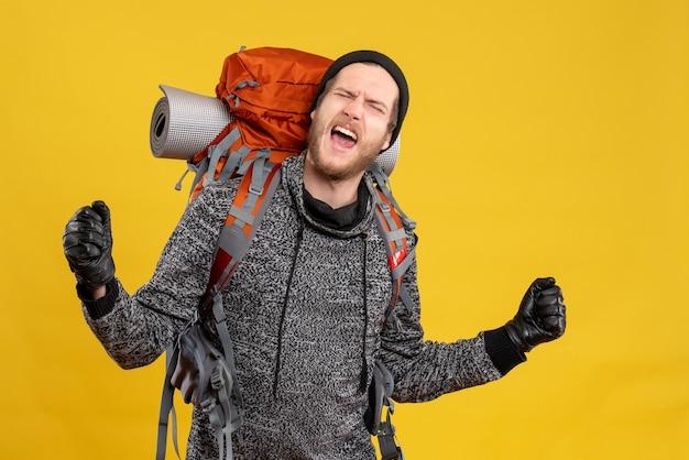 Männlicher tramper mit lederhandschuhen und rucksack, der seine gefühle ausdrückt