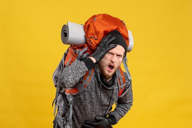 Männlicher tramper mit lederhandschuhen und rucksack mit bauch