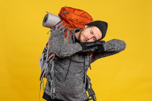 Männlicher tramper mit lederhandschuhen und rucksack schlafen