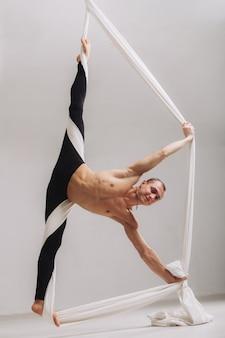 Männlicher turner, der die spalte mit luftseidenbändern tut
