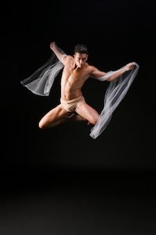 Männlicher turner, der in einer luft springt
