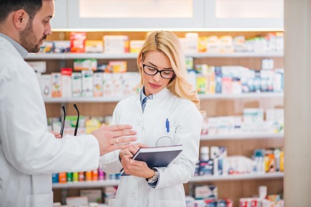 Männlicher und weiblicher apotheker, der medikament in einer drogerie bespricht.