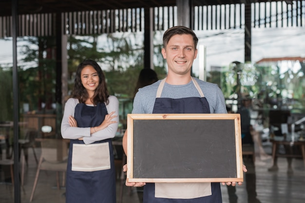 Männlicher und weiblicher cafébesitzer, der stolz vor ihrem café oder café steht, das tafel hält