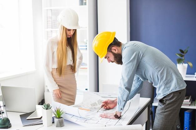 Männlicher und weiblicher ingenieur, der an plan im büro arbeitet