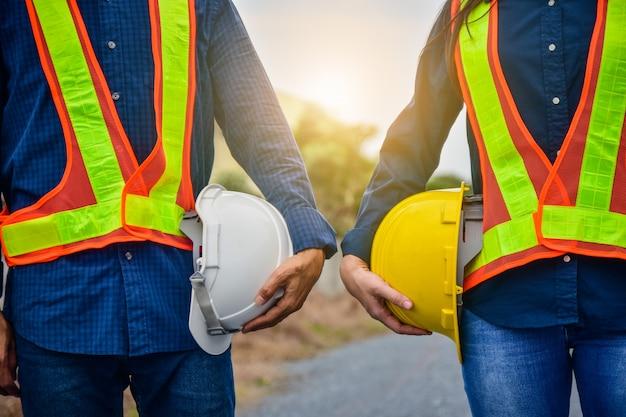 Männlicher und weiblicher ingenieur, der hardhatsicherheit hält
