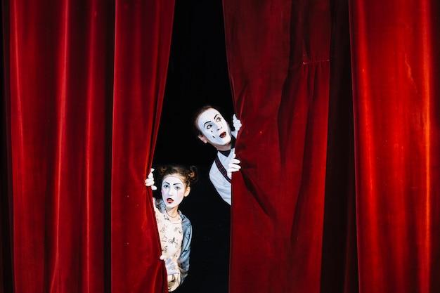 Männlicher und weiblicher pantomimekünstler, der vom roten vorhang späht