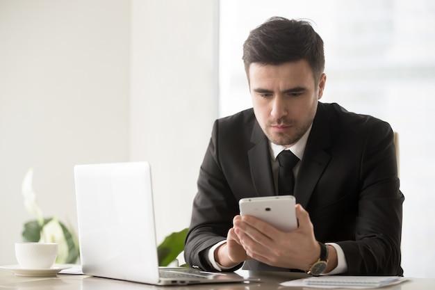 Männlicher unternehmensführer, der online-ressourcen mit hilfe von gadgets durchsucht