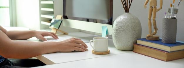 Männlicher unternehmer, der mit computer auf weißem schreibtisch mit vorräten und dekorationen arbeitet