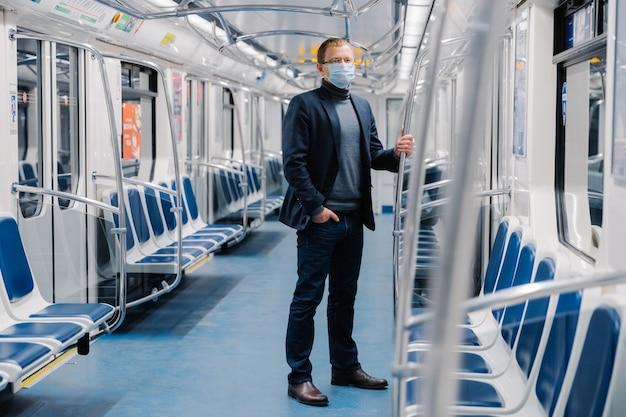 Männlicher unternehmer in formeller klage, medizinischer maske, virenschutz und quarantäne schützt sich im öffentlichen verkehr vor coronavirus