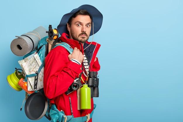 Männlicher urlauber hat aktive ruhe, trägt rucksack mit karte, aufgerollten lappen, trägt lässige touristenkleidung, benutzt ein fernglas