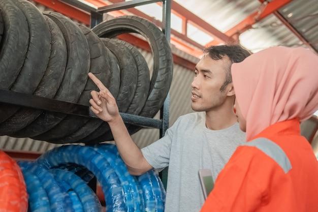 Männlicher verbraucher betrachtet einen reifen, indem er einen finger zeigt, der einen reifen mit einer verschleierten mechanikerin in einer motorradersatzteilwerkstatt auswählt