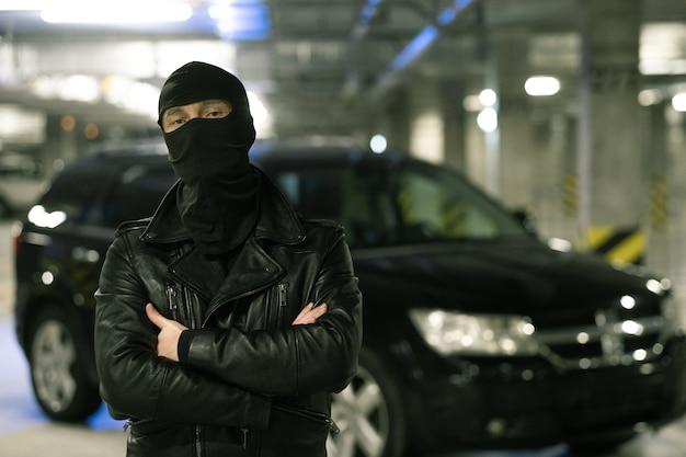 Männlicher verbrecher in schwarzer jacke und sturmhaube auf kopfkreuzungsarmen durch brust mit auto auf parkplatz auf hintergrund