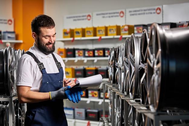 Männlicher verkäufer im autoladen, der notizen macht, das dokument prüft und eigenschaften prüft, rack mit autofelgen betrachtet