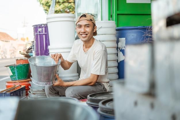 Männlicher verkäufer lächelt, wenn man nach vorne schaut, während man einen eimer im haushaltsgeräte-laden hält