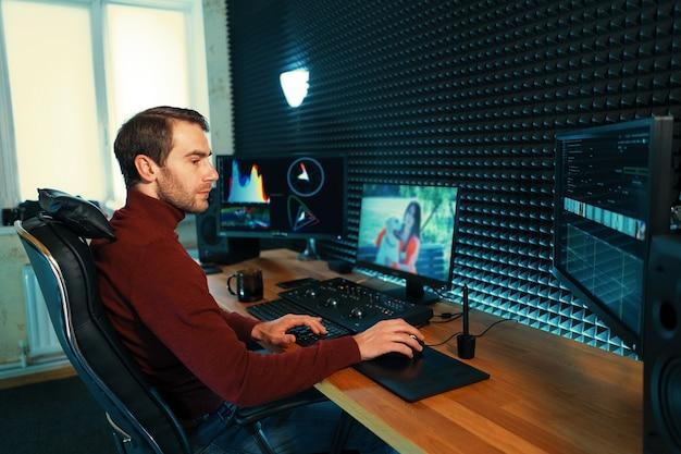 Männlicher videograf bearbeitet und schneidet filmmaterial und ton auf seinem pc