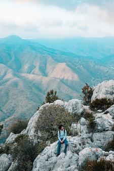 Männlicher wanderer, der allein auf felsiger berglandschaft sitzt