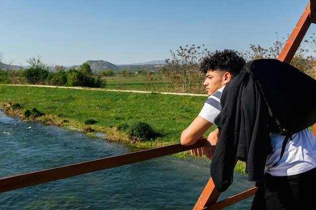 Männlicher wanderer, der auf dem geländer betrachtet idyllischen fluss sich lehnt